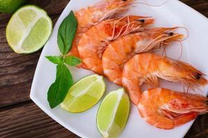 Délicieuses crevettes de fruits de mer frais au citron vert sur le dessus de table en bois