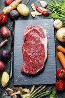fond de nourriture avec des légumes frais et un steak de boeuf cru photo