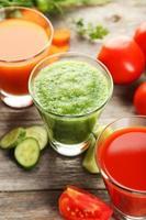 Tomate fraîche, jus de carotte et concombre sur fond de bois gris photo