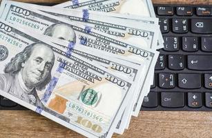 pile de billets de cent dollars sur le clavier photo