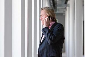 homme d'affaires appelant avec son téléphone portable au bureau blanc. photo