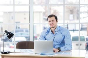 confiance dans le travail. homme d'affaires strict travaillant sur un ordinateur portable photo