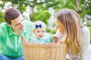 couple heureux avec leur bébé dans un panier à linge photo