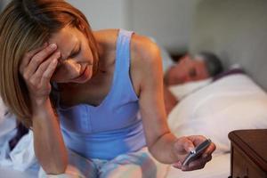 une femme souffrant d'insomnie pendant que son mari dort