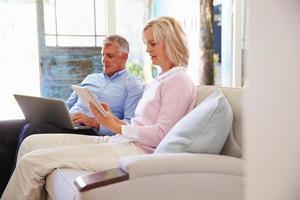 couple mature à la maison dans le salon à l'aide d'appareils numériques