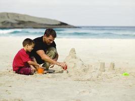 père et fils construisant des châteaux de sable sur la plage.
