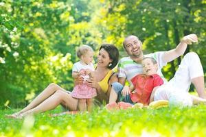 heureux jeune couple avec leurs enfants s'amuser au parc photo