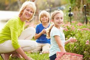 grand-mère avec petits-enfants sur la chasse aux oeufs de pâques dans le jardin