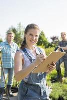 upervisor holding presse-papiers avec jardiniers debout en arrière-plan photo