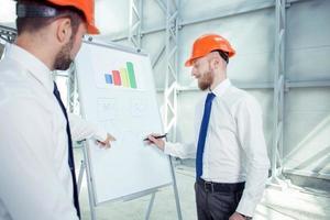 beaux jeunes constructeurs discutent du plan de construction photo