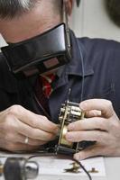 réparateur travaillant sur une vieille horloge photo