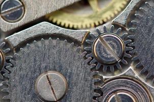 fond avec des roues dentées métalliques une horloge. macro photo