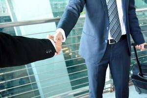 Poignée de main d'hommes d'affaires à l'aéroport - concept de voyage d'affaires photo