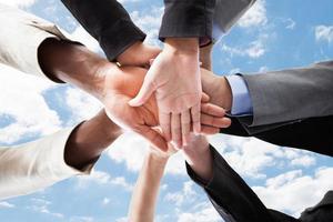 les mains des hommes d'affaires multiethniques les uns sur les autres photo