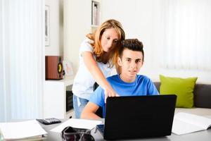 Joyeux jeune femme professeur privé aidant un adolescent à faire ses devoirs photo