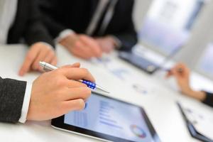 équipe commerciale utilisant une tablette tactile pour travailler avec des données financières