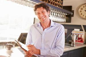 directeur de restaurant masculin tenant le presse-papiers, portrait photo