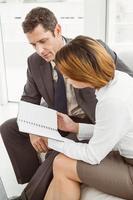 homme d'affaires et secrétaire regardant journal photo