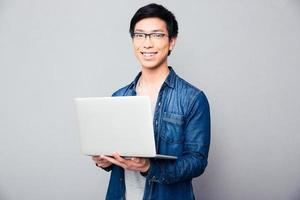 gai, homme asiatique, debout, à, ordinateur portable photo