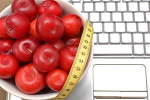 prunes rouges, ordinateur portable et ruban à mesurer