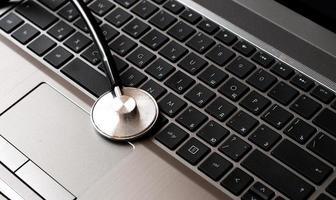 Stéthoscope reposant sur un clavier d'ordinateur - concept en ligne photo