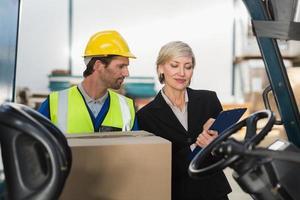directeur d'entrepôt parler avec un conducteur de chariot élévateur