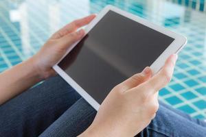 femme travaillant avec tablette assis à la piscine