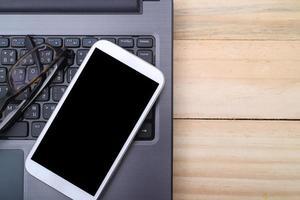 lieu de travail de bureau avec ordinateur portable et téléphone intelligent sur table en bois photo