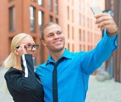 employés de bureau prenant selfie avec téléphone portable.