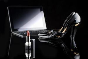 ordinateur portable, rouge à lèvres et chaussures. fond noir. ensemble féminin. achat en ligne photo