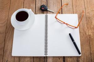 nootbook vierge avec tasse à café et accessoires sur vieux bois photo