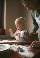 petit boulanger avec grand-mère prépare des biscuits de Noël photo