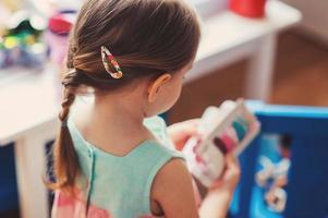 fille enfant en bas âge à la maison, vue arrière avec des accessoires pour cheveux photo