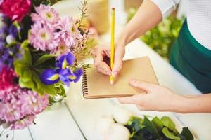 fleuriste avec bloc-notes et crayon photo