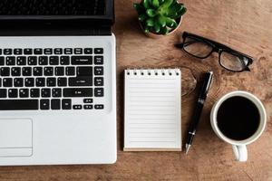 ordinateur portable et tasse de café sur la vieille table en bois photo