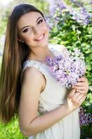 belle fille avec des fleurs lilas photo