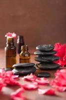 huile essentielle azalée fleurs pierres de massage noires photo