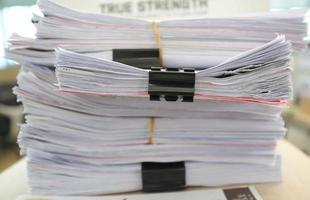 de nombreux tas de papiers sur le bureau photo