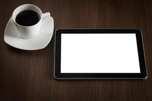 tablette et tasse de café sur la table de bureau. photo