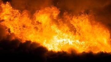 brûler la flamme du feu sur le toit de la maison en bois
