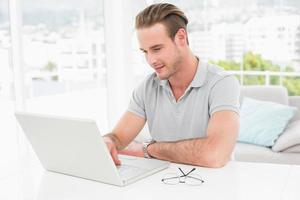 homme d'affaires décontracté souriant et utilisant un ordinateur portable
