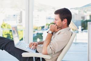 homme d'affaires détendu avec un ordinateur portable