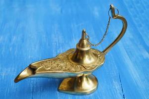 lampe de génie magique isolé sur un fond en bois bleu photo