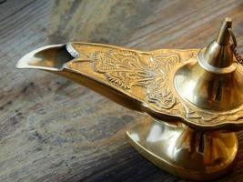 lampe de génie magique isolé sur un fond en bois photo