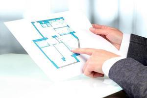 agent immobilier montrant des plans de maison à un homme d'affaires. photo
