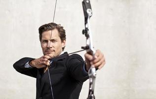 homme d'affaires visant l'arc et la flèche photo