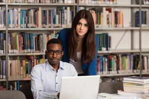 étudiants heureux travaillant avec un ordinateur portable dans la bibliothèque photo