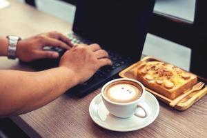 homme d'affaires travaille avec un ordinateur portable, tenant un téléphone mobile photo