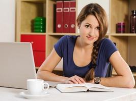 belle femme lisant et utilisant un ordinateur portable photo