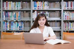 belle étudiante asiatique utilisant un ordinateur portable pour étudier dans la bibliothèque